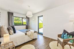 Home Staging Eingerichtetes Zimmer mit Bett, Sessel und Lampen